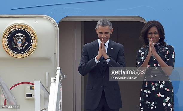 US President Barack Obama and First Lady Michelle Obama gesture as they board Air Force One prior to departing from Air Force Station Palam in New...