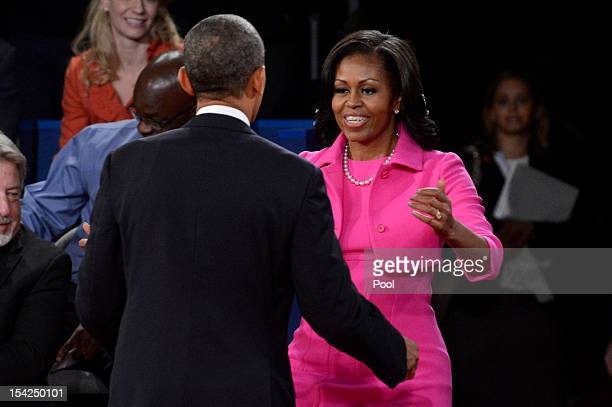 S President Barack Obama and first lady Michelle Obama go to embrace after a town hall style debate at Hofstra University October 16 2012 in...