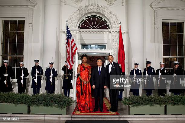 President Barack Obama and first lady Michelle Obama greet Chinese President Hu Jintao at the Grand Staircase as they arrive for a state dinner at...
