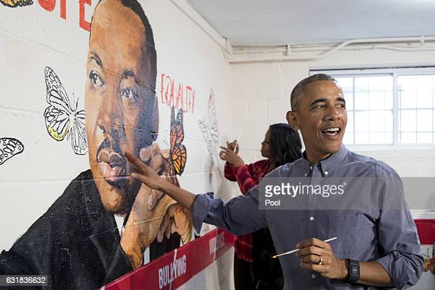 US President Barack Obama and first lady Michelle Obama help paint a mural depicting Martin Luther King Jr at the Jobs Have Priority Naylor Road...