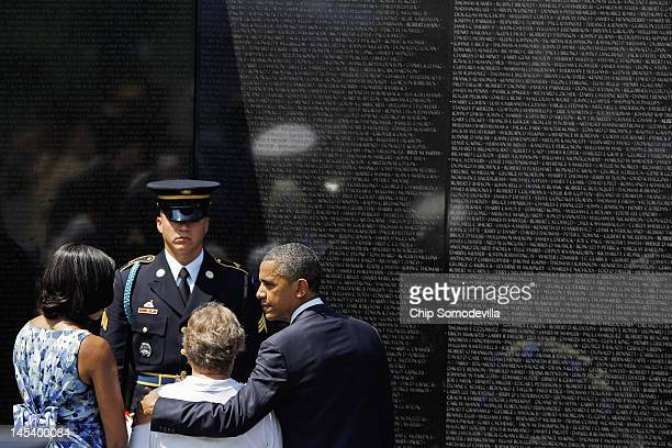 S President Barack Obama and first lady Michelle Obama help Rose Mary SaboBrown place a wreath at the Vietnam Veterans Memorial during a Memorial Day...