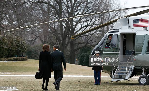 S President Barack Obama and first lady Michelle Obama hold hands as they walk to Marine One while departing the White House March 7 2014 in...