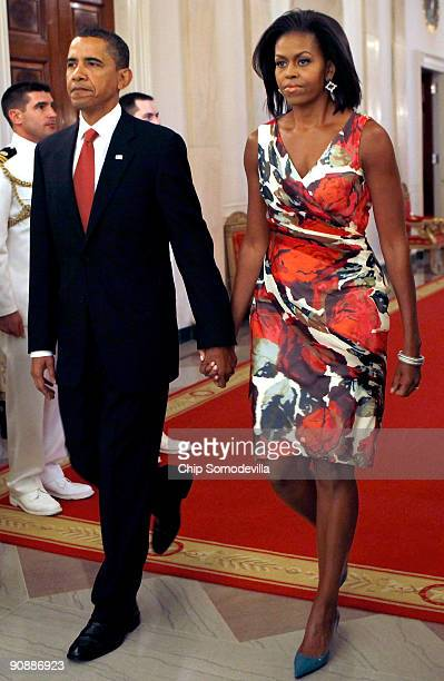 S President Barack Obama and first lady Michelle Obama hold hands as they arrive for the Medal of Honor ceremony for US Army Sergeant First Class...