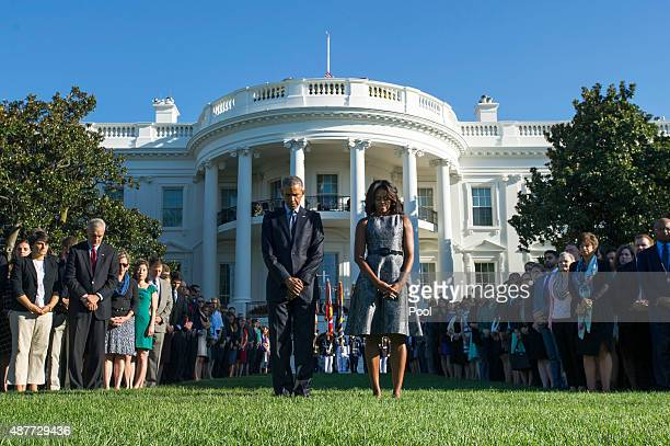S President Barack Obama and First Lady Michelle Obama joined by White House staff participate in a moment of silence on the 14th anniversary of the...