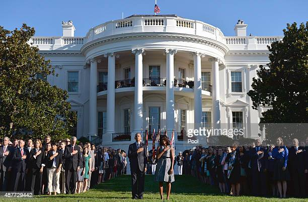 S President Barack Obama and First Lady Michelle Obama joined by White House staff stand as Taps is played on the 14th anniversary of the September...