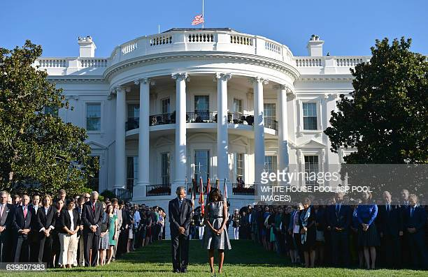 President Barack Obama and First Lady Michelle Obama joined by White House staff participate in a moment of silence on the 14th anniversary of the...