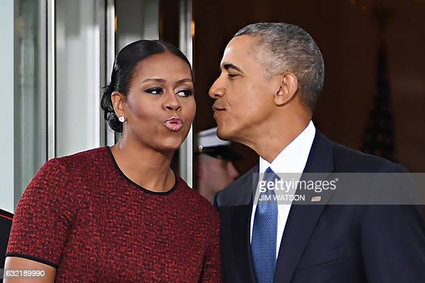 President Barack Obama and First Lady Michelle Obama kiss as they prepare to greet Presidentelect Donald Trump and his wife Melania to the White...