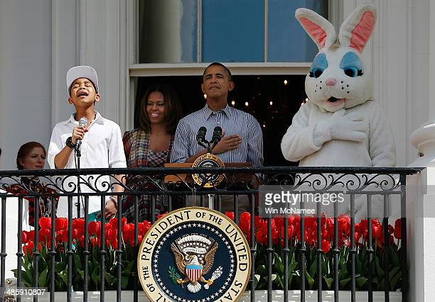 S President Barack Obama and first lady Michelle Obama listen as Cam Anthony sings the national anthem at the annual White House Easter Egg Roll on...