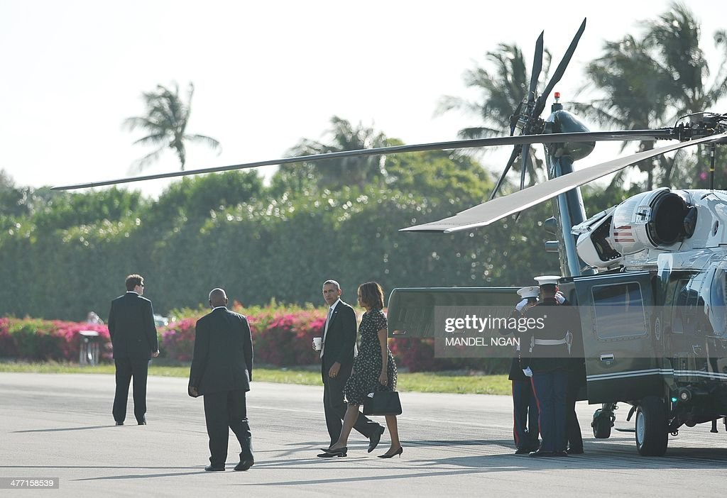 US President Barack Obama and First Lady Michelle Obama make their way from Marine One upon arrival at Key Largo, Florida on March 7, 2014. . AFP PHOTO/Mandel NGAN