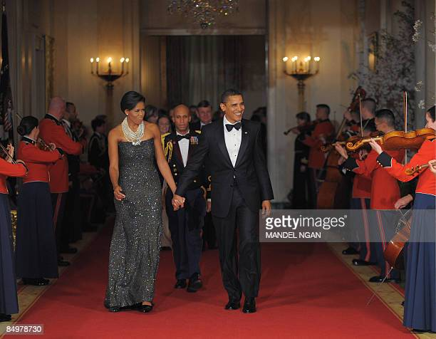President Barack Obama and First Lady Michelle Obama make their way into the East Room for after dinner entertainment with US governors February 22,...