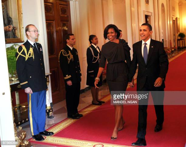 US President Barack Obama and First Lady Michelle Obama make their way into the East Room for a reception marking International Women�s Day March 8...
