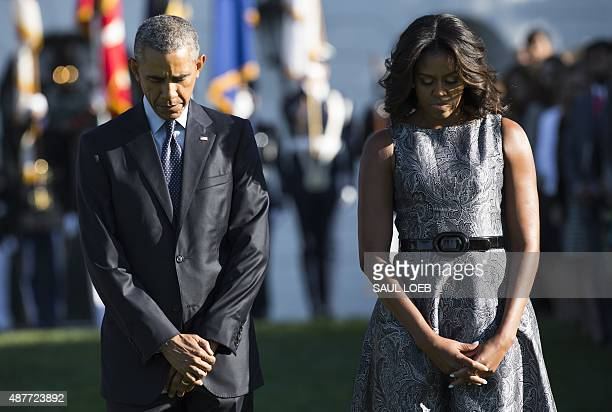 US President Barack Obama and First Lady Michelle Obama observe a moment of silence on the South Lawn of the White House in Washington DC September...