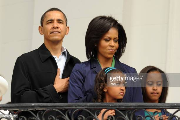 US President Barack Obama and first lady Michelle Obama observe the US National Anthem with their two daughters Sasha Obama and Malia Obama before...
