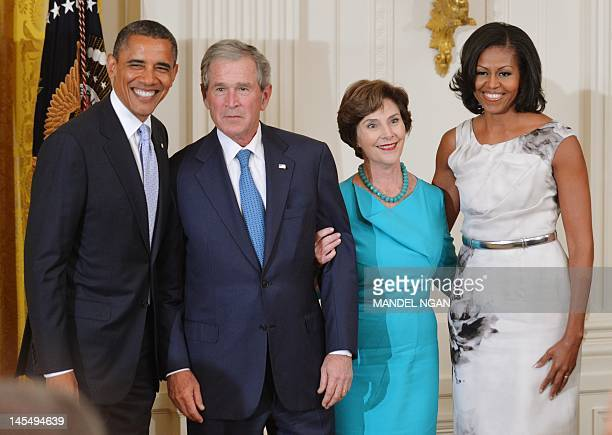 US President Barack Obama and First Lady Michelle Obama pose with former US president George W Bush and his wife Laura Bush during the unveiling of...