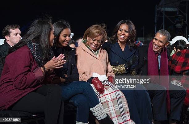 US President Barack Obama and First Lady Michelle Obama share a laugh with their daughters Malia and Sasha and Marion Robinson Michelle Obama's...