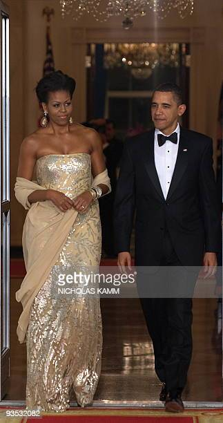 US President Barack Obama and First Lady Michelle Obama shortly walk out to greet Indian Prime Minister Manmohan Singh and his wife Gursharan Kaur at...