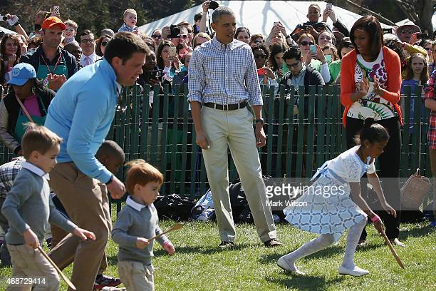 President Barack Obama and first lady Michelle Obama shout encouragement as young participants roll eggs during the White House Easter Egg Roll on...