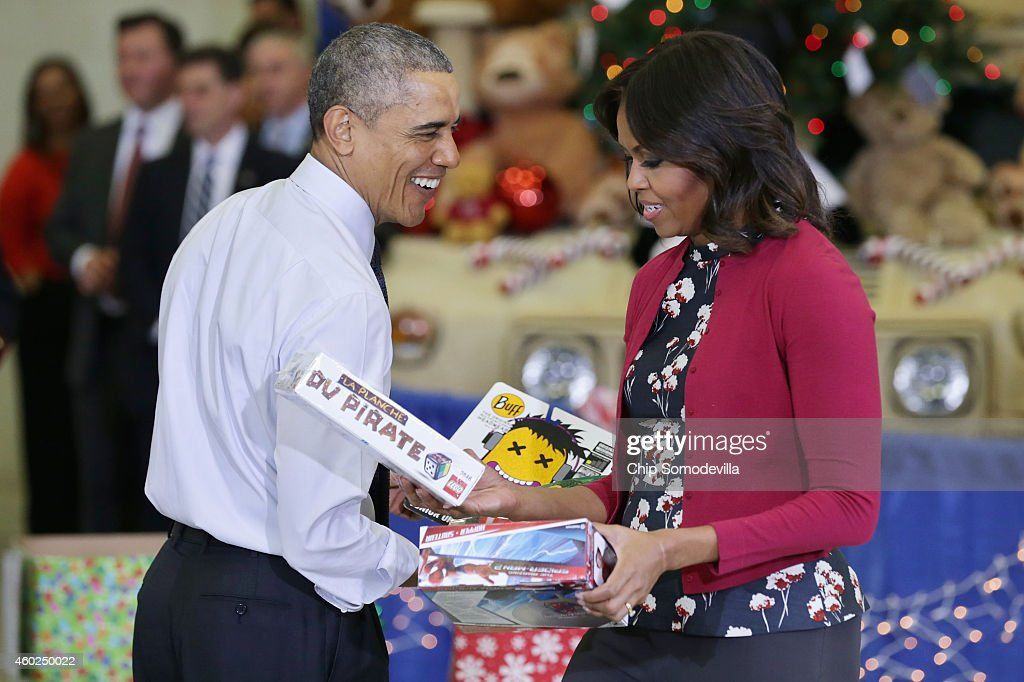 U.S. President Barack Obama (L) and first lady Michelle Obama sort toys and gifts donated by Executive Office of the President staff to the Marine Corps Reserve Toys for Tots Program at Joint Base Anacostia-Bolling on December 10, 2014 in Washington, DC. For 67 years the Toys for Tots program has worked with local communities to collect and distribute toys and gifts for less fortunate children throughout the United States.