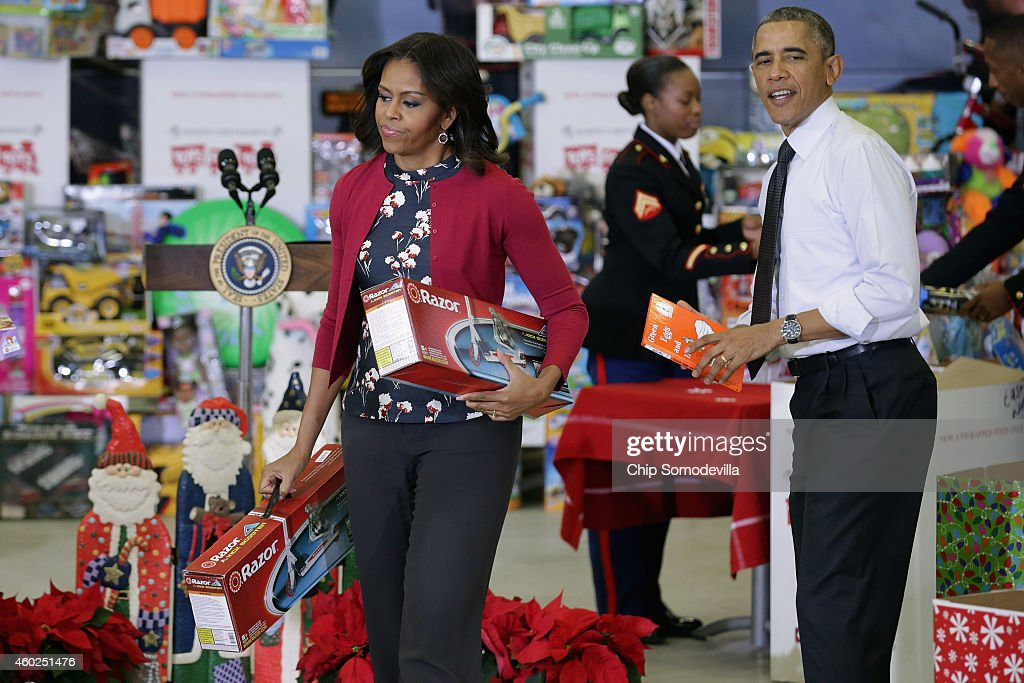 US President Barack Obama (R) and first lady Michelle Obama sort toys and gifts donated by Executive Office of the President staff to the Marine Corps Reserve Toys for Tots Program at Joint Base Anacostia-Bolling December 10, 2014 in Washington, DC. For 67 years the Toys for Tots program has worked with local communities to collect and distribute toys and gifts for less fortunate children throughout the United States.