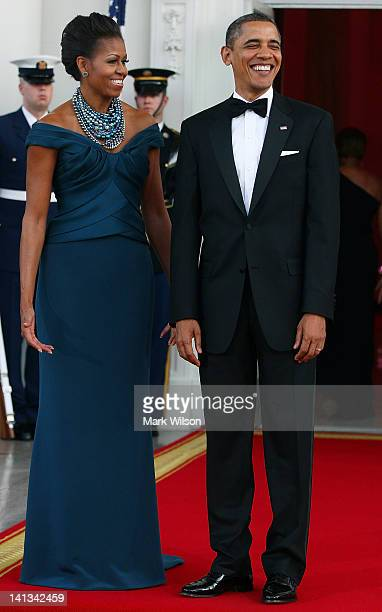 S President Barack Obama and first lady Michelle Obama stand in the North Portico of the White House before attending a state dinner March 14 2012 in...