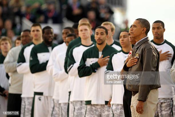 S President Barack Obama and first lady Michelle Obama stand next to the Michigan State Spartans during the United States National Anthem before the...