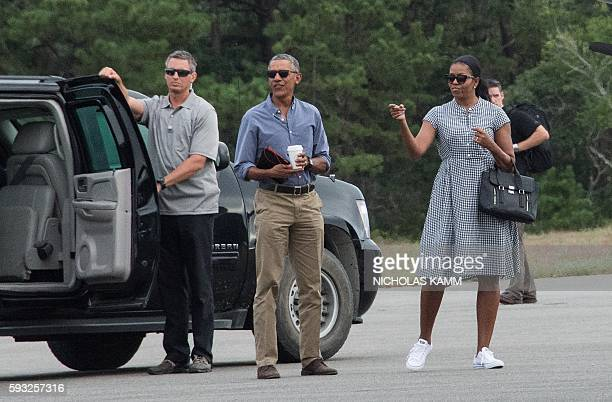 US President Barack Obama and First Lady Michelle Obama wait for their daughters Malia and Sasha to board Marine One at Martha's Vineyard airport in...