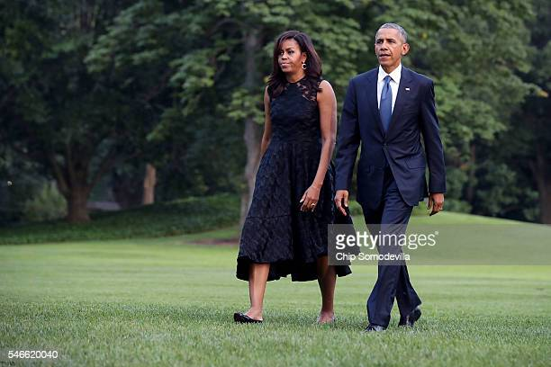 US President Barack Obama and first lady Michelle Obama walk across the South Lawn after returning to the White House on Marine One July 12 2016 in...