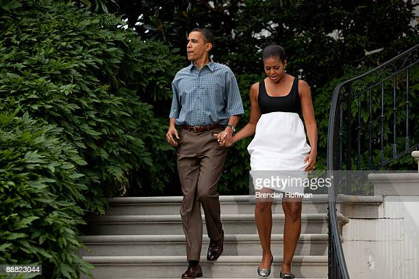 President Barack Obama and First Lady Michelle Obama walk down the steps of the White House to shake hands with guests at a gathering of military...