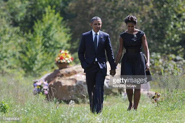 President Barack Obama and First Lady Michelle Obama walk hand in hand on September 11, 2011 as they visit the crash site after attending in a...