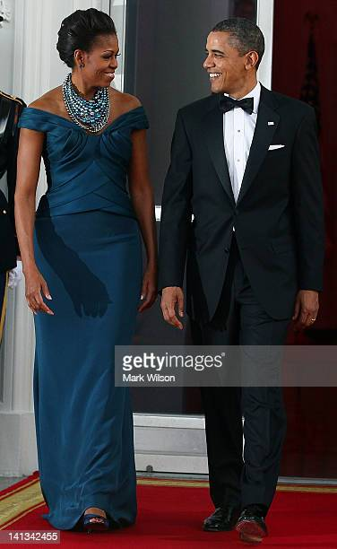 S President Barack Obama and first lady Michelle Obama walk into the North Portico of the White House before attending a state dinner March 14 2012...