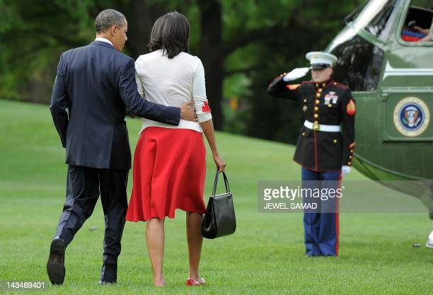 US President Barack Obama and First Lady Michelle Obama walk on the South Lawn at the White House to board Marine One on April 27 2012 in Washington...