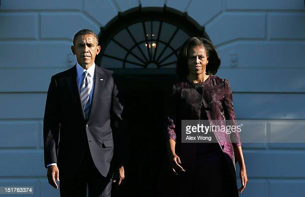 President Barack Obama and first lady Michelle Obama walk out from the residence to observe a moment of silence with White House staff to mark the...