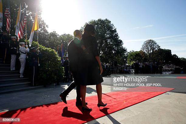 S President Barack Obama and first Lady Michelle Obama walk out to welcome Pope Francis prior to his arrival ceremony at the White House on September...