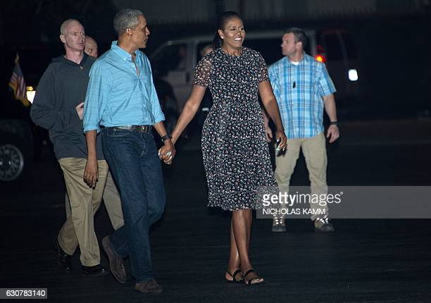 US President Barack Obama and First Lady Michelle Obama walk to board Air Force One at Joint Base Pearl HarborHickam in Honolulu on January 1 2017 as...