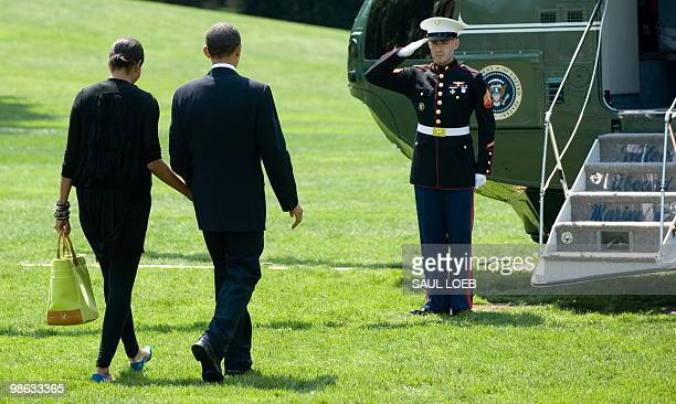 US President Barack Obama and First Lady Michelle Obama walk to Marine One prior to departing from the South Lawn of the White House in Washington DC...