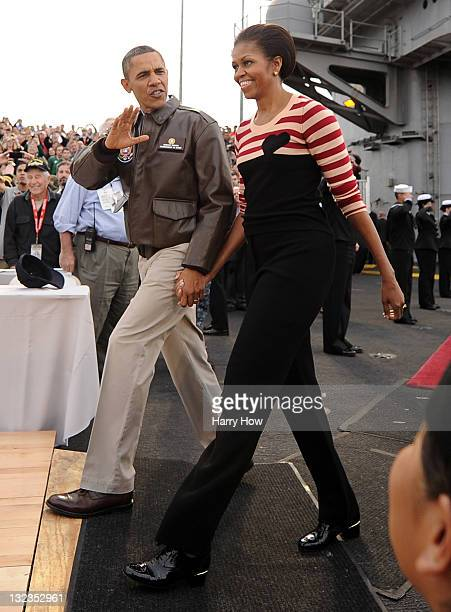 S President Barack Obama and first lady Michelle Obama walk to the court before the start of the NCAA men's college basketball Carrier Classic...