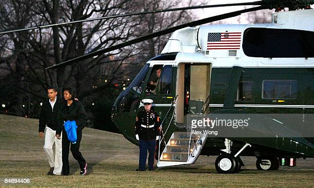S President Barack Obama and First Lady Michelle Obama walk toward their residence after they got off from Marine One at the South Lawn of the White...