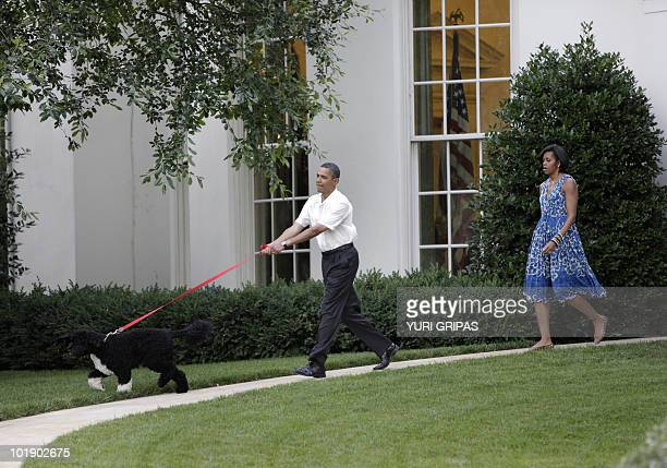 US President Barack Obama and First Lady Michelle Obama walk with the first family's dog as they arrive at the Congressional Picnic on the South Lawn...