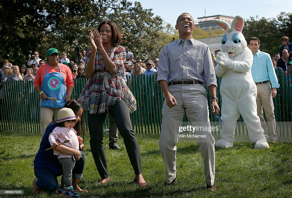 U.S. President Barack Obama and first lady Michelle Obama watch children participate in the annual White House Easter Egg Roll on the South Lawn April 21, 2014 in Washington, DC. President Obama and the first lady hosted thousands of children for the annual White House event dating back to 1876 that features live music, sports courts, cooking stations, storytelling, as well as the Easter egg roll this year.