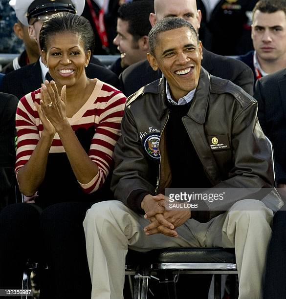 US President Barack Obama and First Lady Michelle Obama watch on the flight deck of the USS Carl Vinson during the Carrier Classic college basketball...