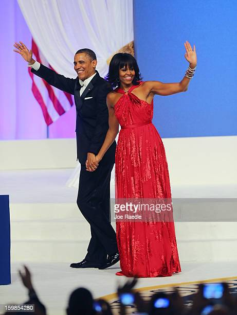 S President Barack Obama and first lady Michelle Obama wave after dancing during the CommanderInChief's Inaugural Ball January 21 2013 in Washington...