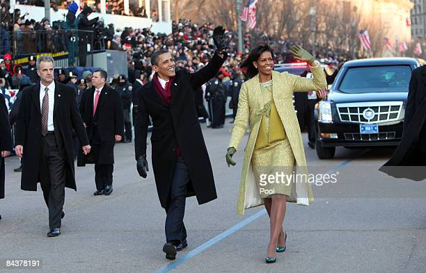 S President Barack Obama and first lady Michelle Obama wave as they walk in the inaugural parade following his inauguration as the 44th President of...