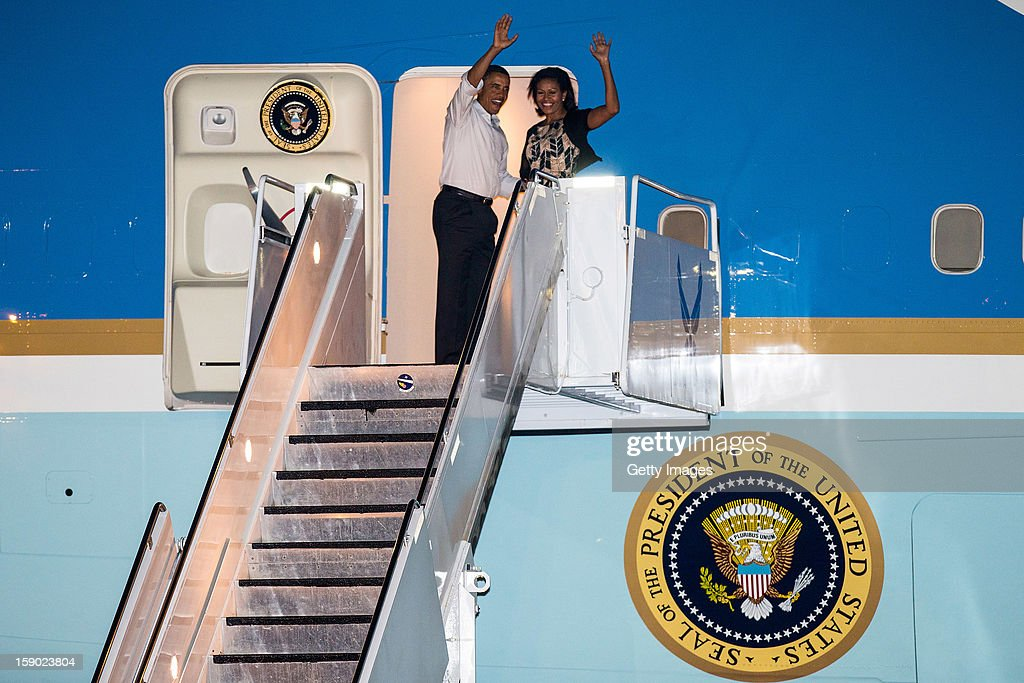 US President Barack Obama and First Lady Michelle Obama wave as they board Air Force One at Joint Base Pearl Harbor-Hickam on January 5, 2013 in Honolulu, Hawaii. The president had to cut short his vacation to work in Washington on efforts to avert the recent fiscal cliff crisis and then returned to Hawaii to be with his family.