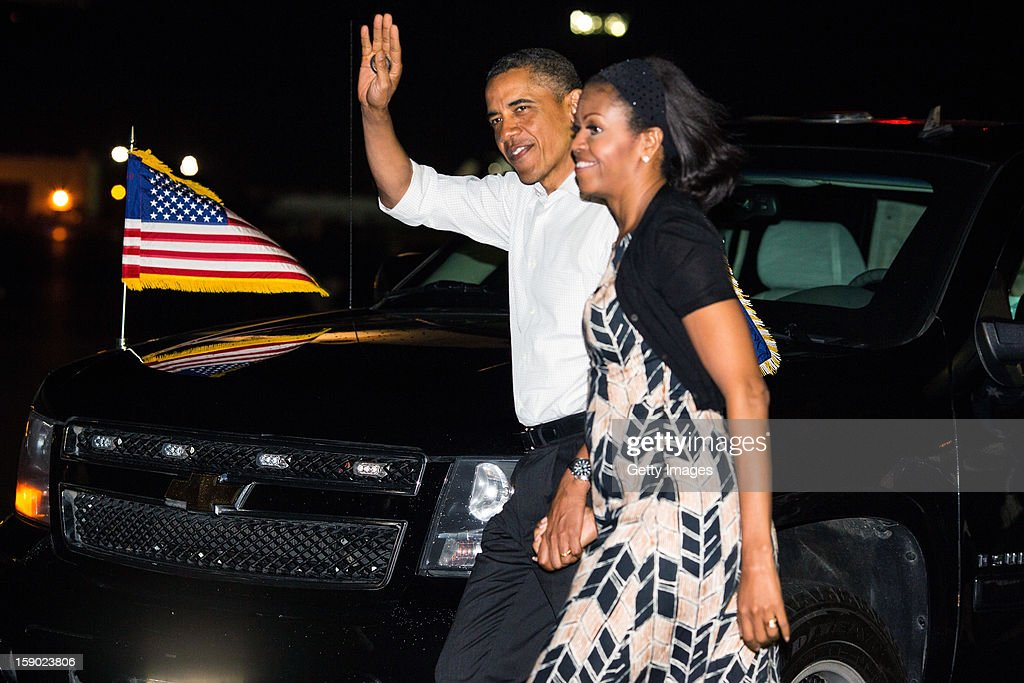 US President Barack Obama and First Lady Michelle Obama wave before boarding Air Force One at Joint Base Pearl Harbor-Hickam on January 5, 2013 in Honolulu, Hawaii. The president had to cut short his vacation to work in Washington on efforts to avert the recent fiscal cliff crisis and then returned to Hawaii to be with his family.