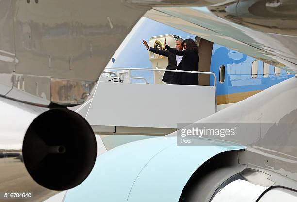 US President Barack Obama and first lady Michelle Obama wave goodbye as they board Air Force One at Joint Base Andrews on their way to Cuba March 20...