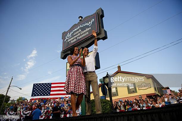 US President Barack Obama and First Lady Michelle Obama wave to supporters as they arrive to deliver remarks during a campaign event in Davenport...