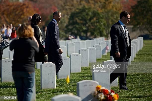 S President Barack Obama and first lady Michelle walk through Arlington National Cemetery after greeting family members of fallen service men and...
