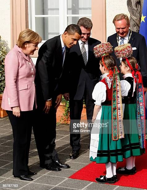 S President Barack Obama and German Chancellor Angela Merkel are welcomed by girls in traditional Black Forrest clothes upon Obama's arrival for...