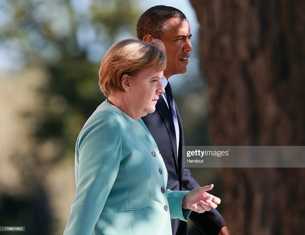 U.S. President Barack Obama (R) and German Chancellor Angela Merkel arrive to pose with other leaders for a group photo during the G20 summit on September 6, 2013 in St. Petersburg, Russia. Leaders of the G20 nations made progress on tightening up on multinational company tax avoidance, but remain divided over the Syrian conflict as they enter the final day of the Russian summit.