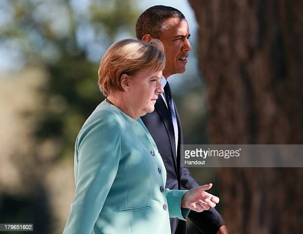 S President Barack Obama and German Chancellor Angela Merkel arrive to pose with other leaders for a group photo during the G20 summit on September 6...